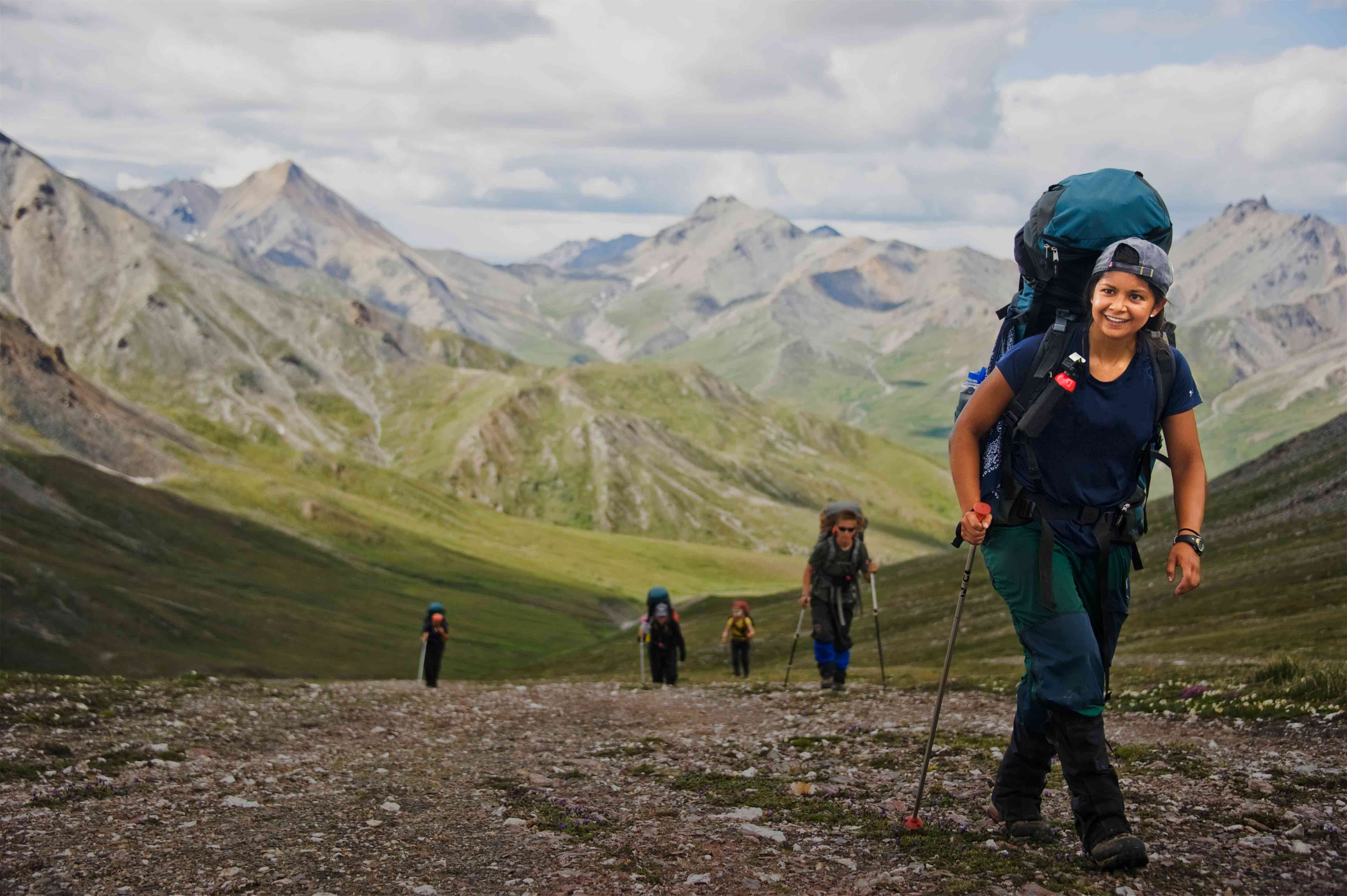 Happy person backpacking in Alaska with a group of peers