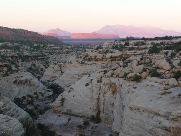 Canyonlands in Utah with sun rising over reddish rock formation in the distance