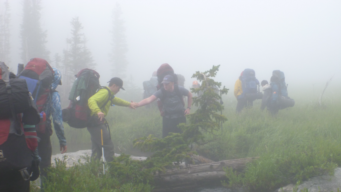 A group of backpackers cross a foggy field in the Bighorn Mountain Range in Wyoming. One boy helps another across a log.