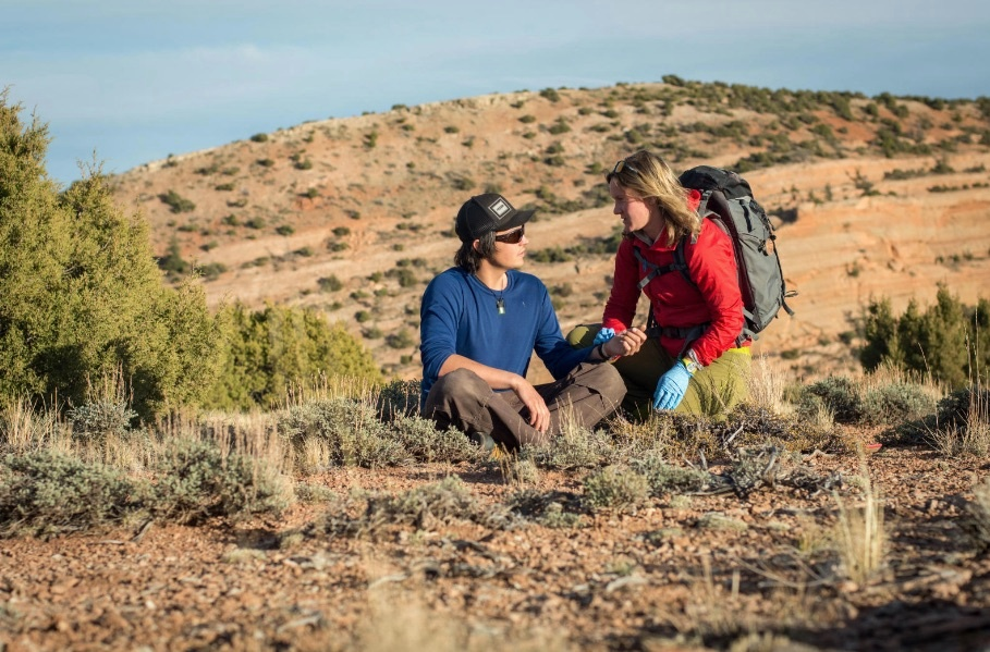 Woman checks the pulse of a man in the outdoors for wilderness first aid