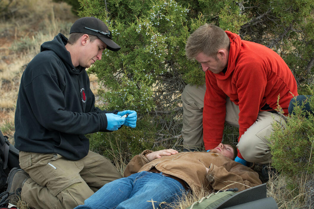 Two responders take the vitals of a patient in the backcountry.
