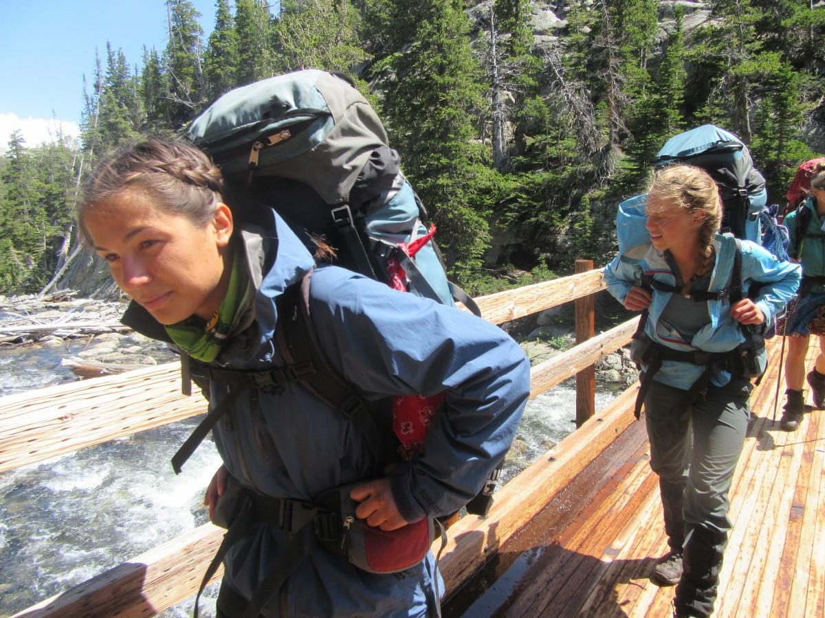 Girls hiking across a bridge with backpacks