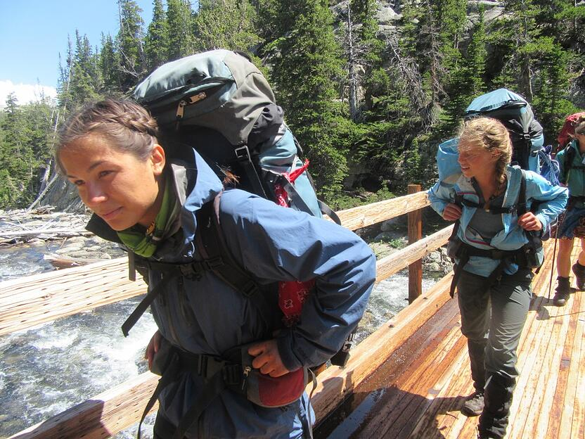 Girls hiking across a bridge with backpacks