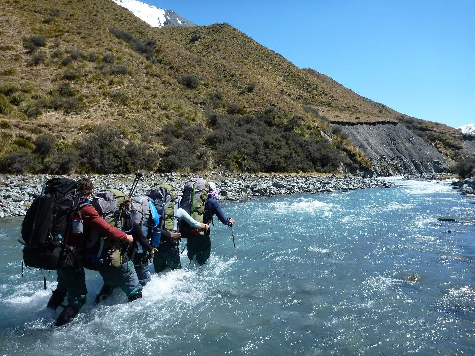 A group of backpackers crosses a river using the eddy line method