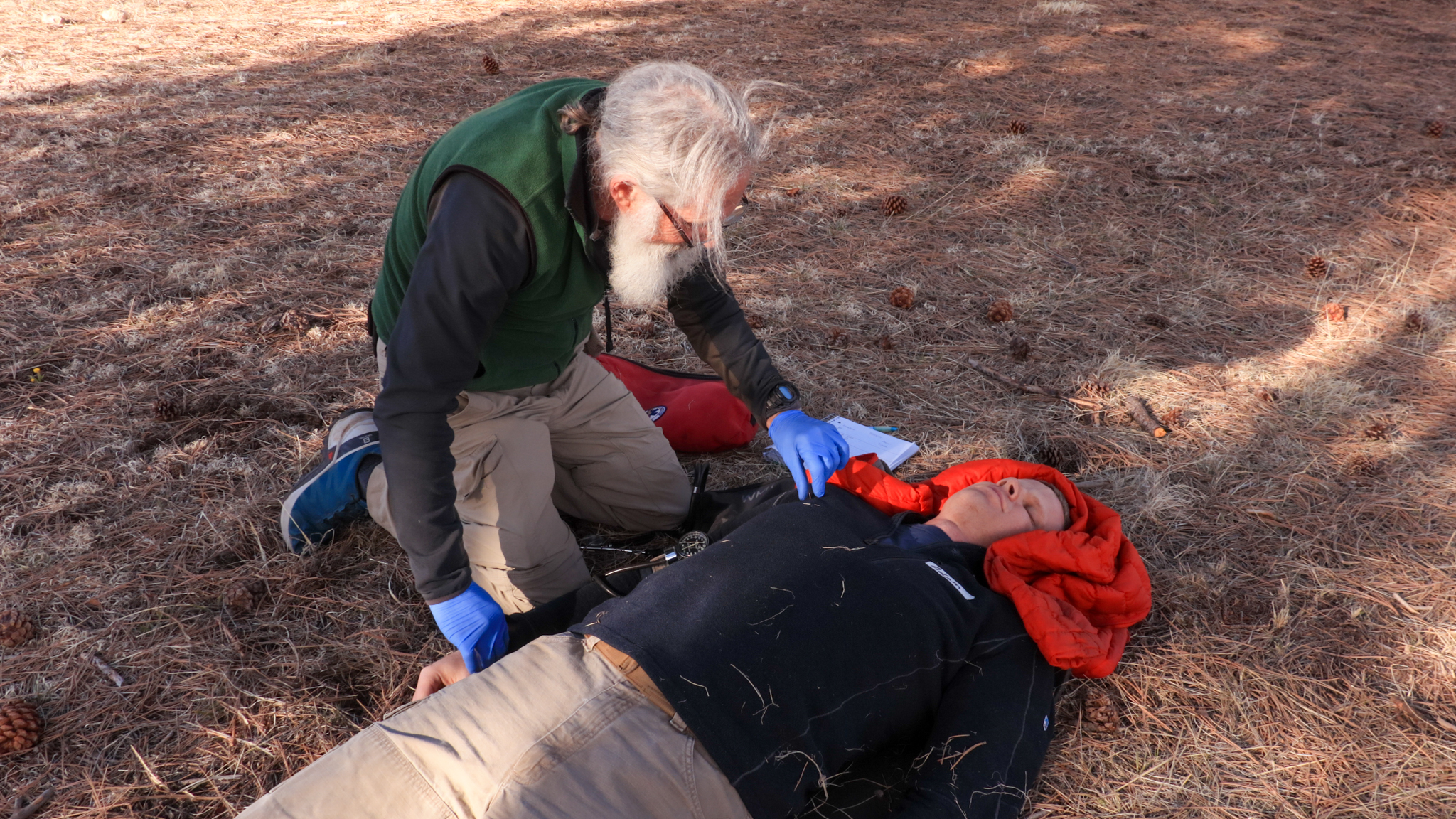 An older man checks the pulse of the an unconscious patient. The patient's neck is stabilized by a coat.
