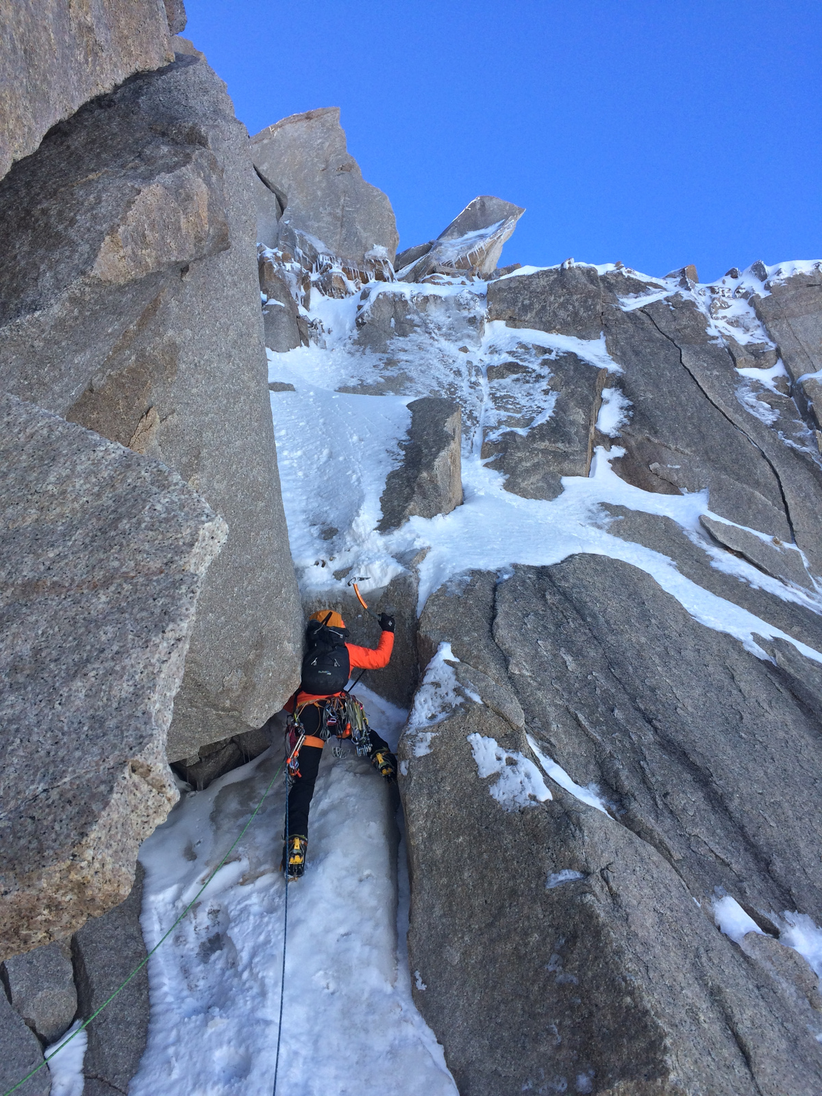 mountaineer in a climbing harness uses ice axe to ascent snow and rock in Patagonia