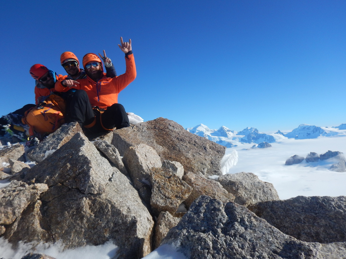 three mountaineers in orange jackets and helmets sit on a rock outcropping at Pantagruel's summit