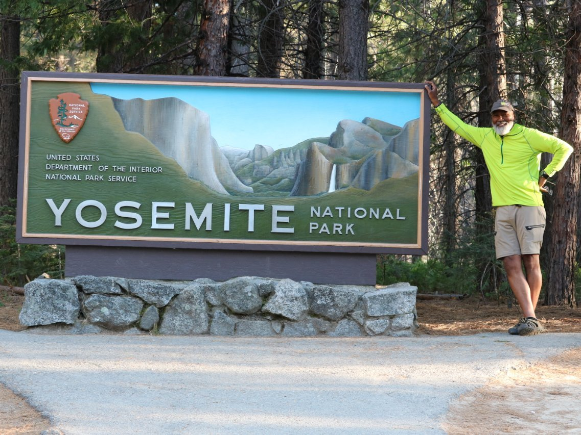 Carter poses at the entrance sign to Yosemite National Park