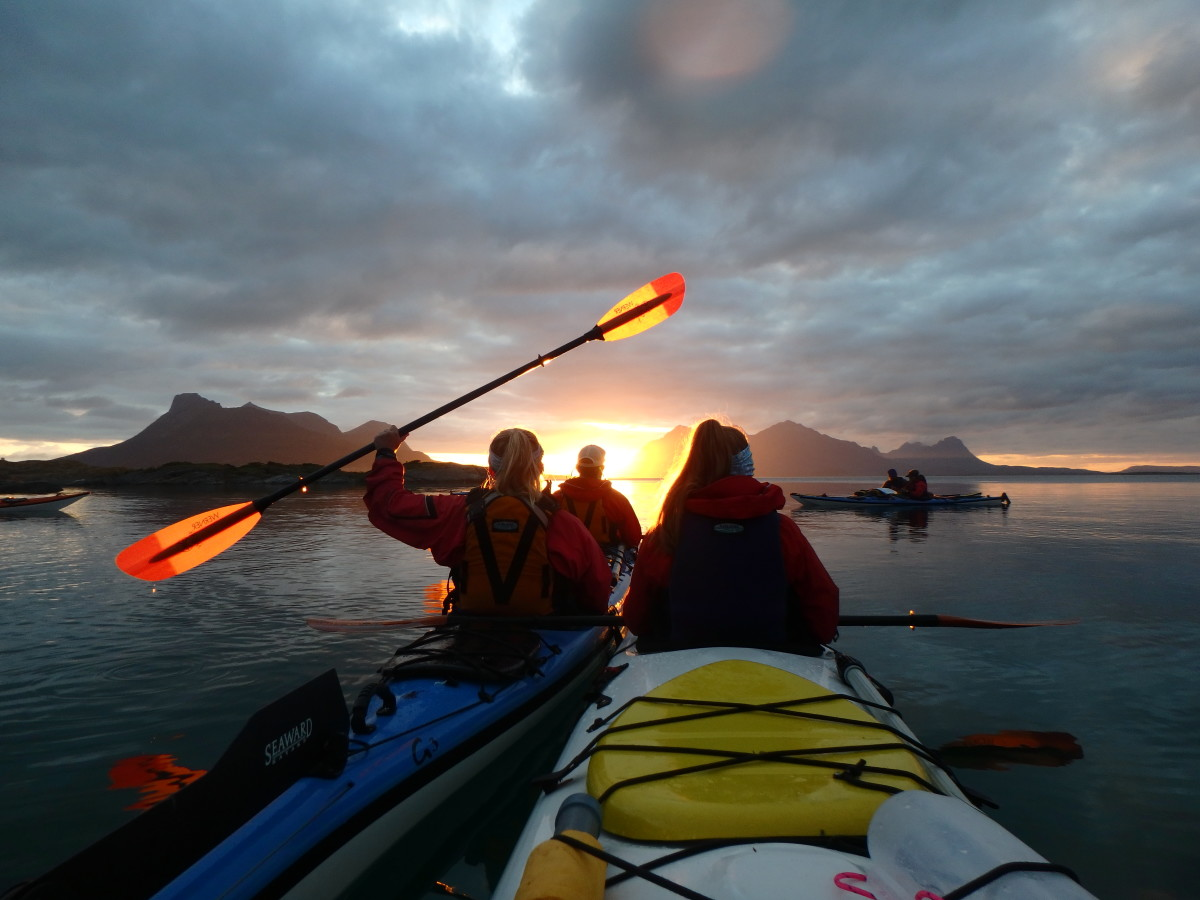 paddlers in kayaks in Scandinavia as sun sets over mountains and dark clouds