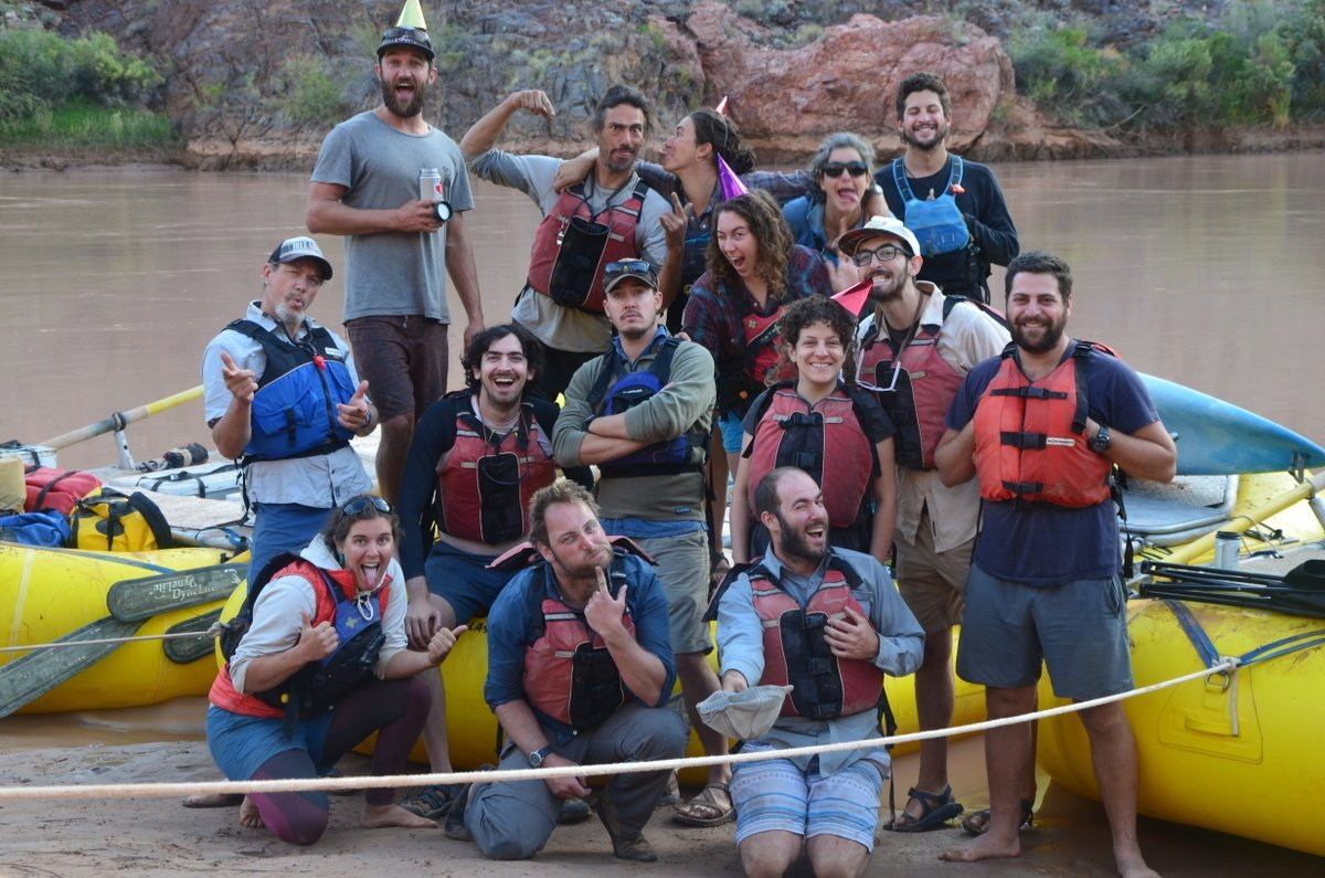 Group photo in front of rafts on a river