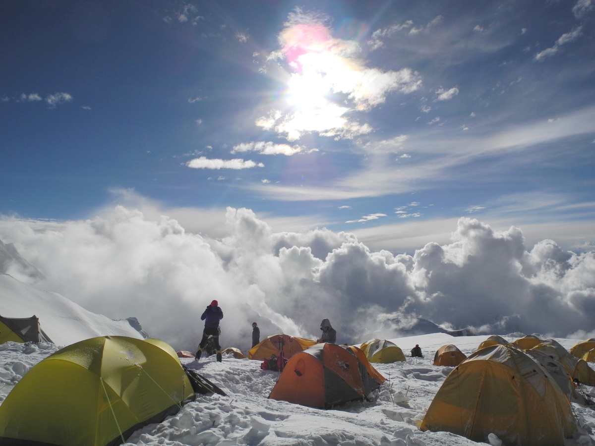 Cluster of yellow and orange tents in a snowy mountain climbing camp shrouded by clouds