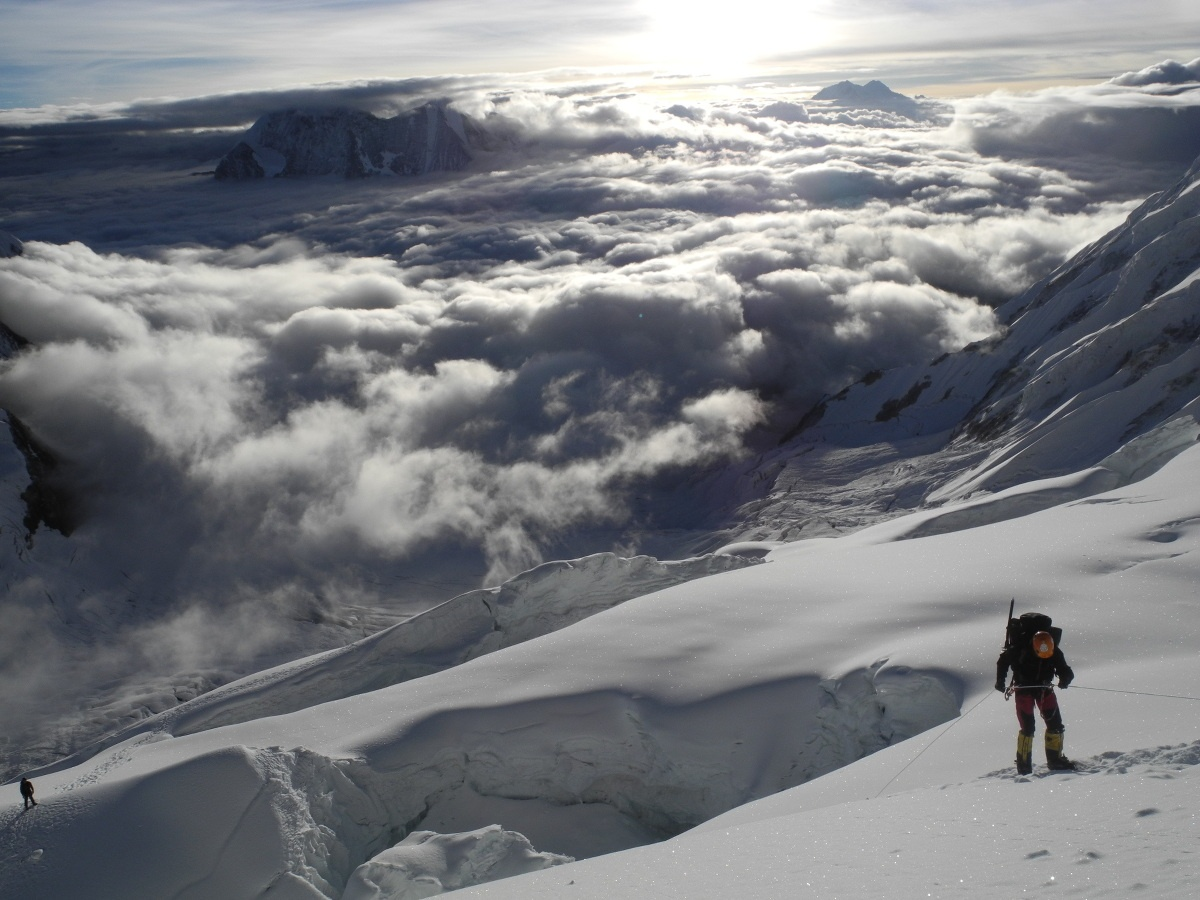Woman mountaineering on a snowy slope high in the mountains with puffy white clouds