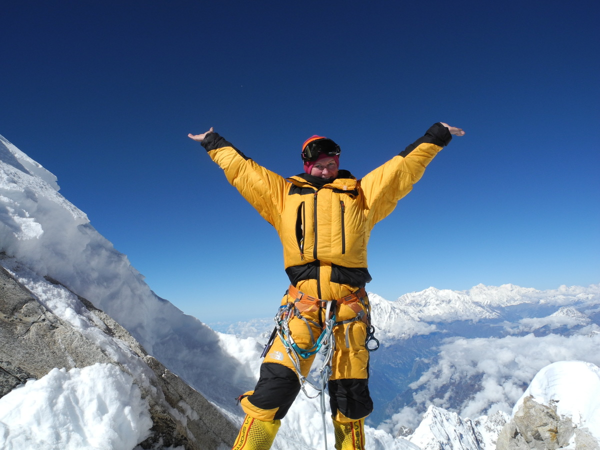 Woman wearing yellow snow gear smiles and raises her arms in the air on a sunny day high in the mountains