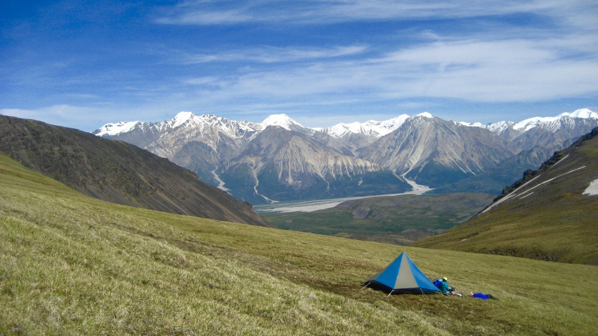 Blue and tan mega mid tent set up on a grassy slope in Alaska with snow-capped peaks beyond