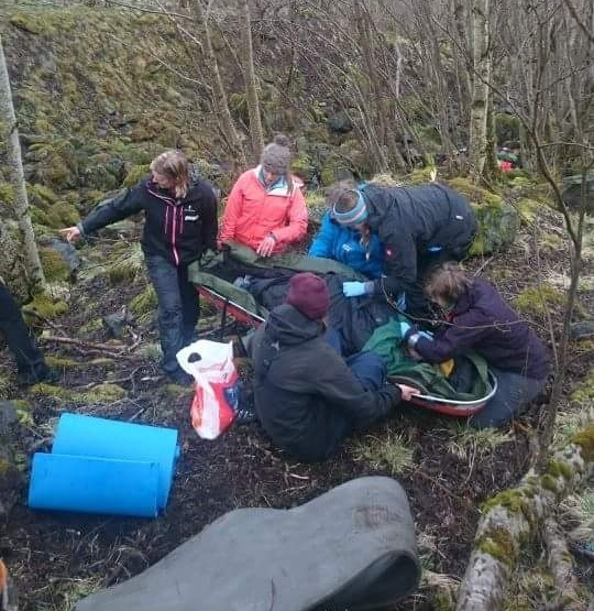 Five wilderness medicine students practice caring for a mock patient in a wooded area