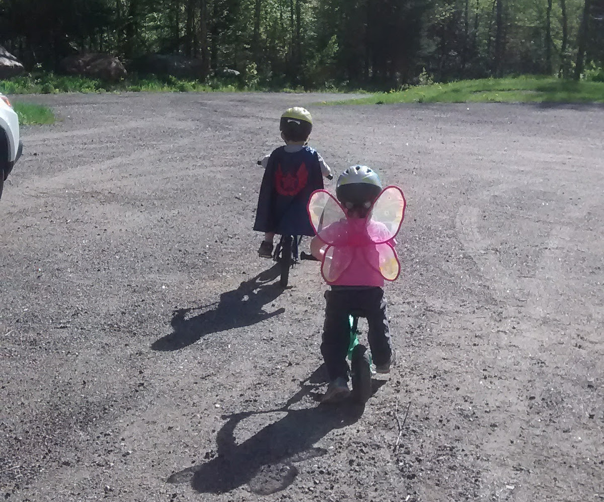 two small children riding bikes, one with superhero cape and one with pink butterfly wings, both wearing helmets