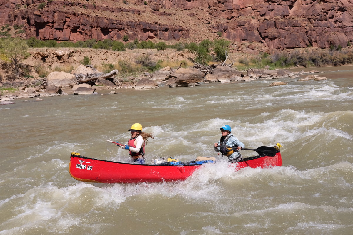 NOLS student and instructor paddle a red canoe through a rapid in a river canyon