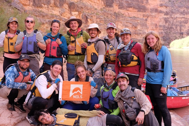 Author's group smiles for a group shot holding an orange NOLS flag while canoeing the Green River