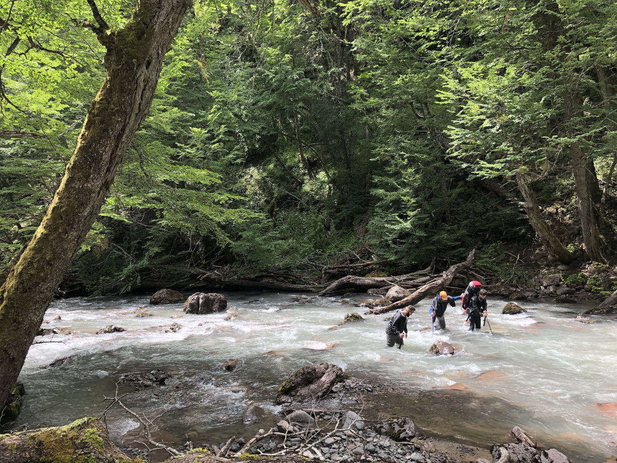 three students work together and use trekking poles to cross a creek in the mountains