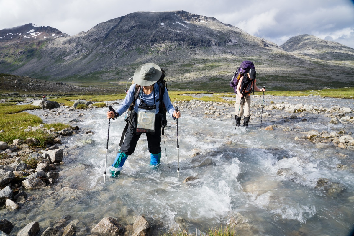 Two people cross a river using trekking poles