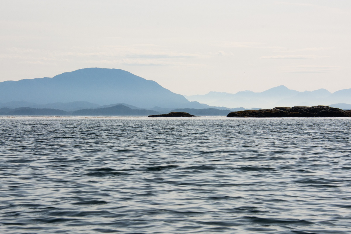 calm slate-colored water with hazy mountains in the distance