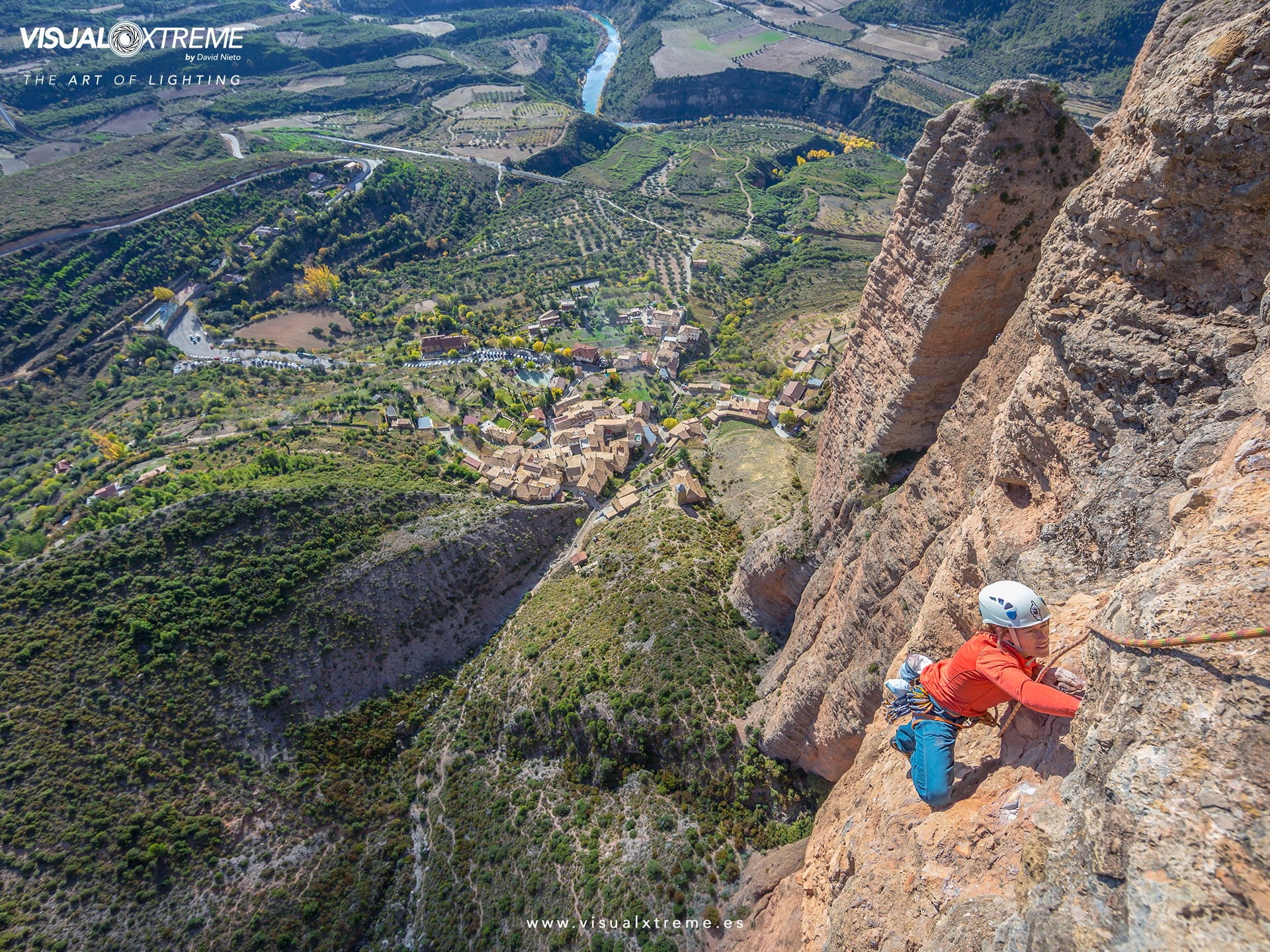 woman rock climbs on reddish rock face high above a small town