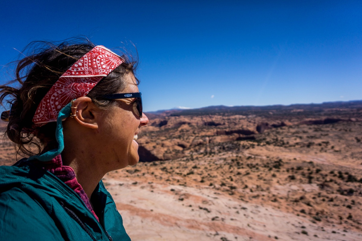 Woman wearing red bandana and sunglasses looks out at desert landscape on a sunny day