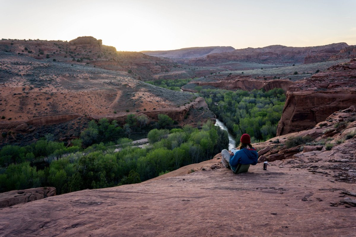 NOLS student sits on flat red rock formation looking out at green trees lining a red rock canyon and writes in her journal