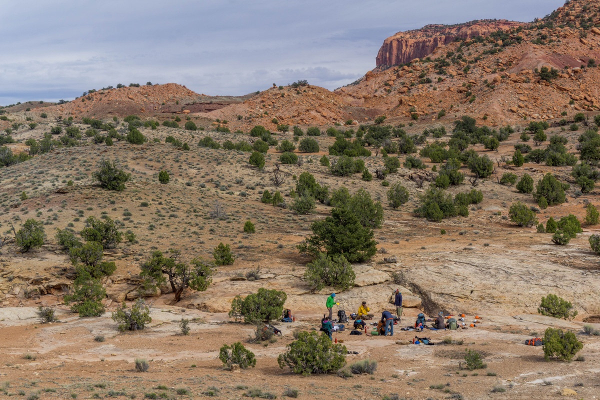 Group of students circles up at camp in Utah's canyonlands