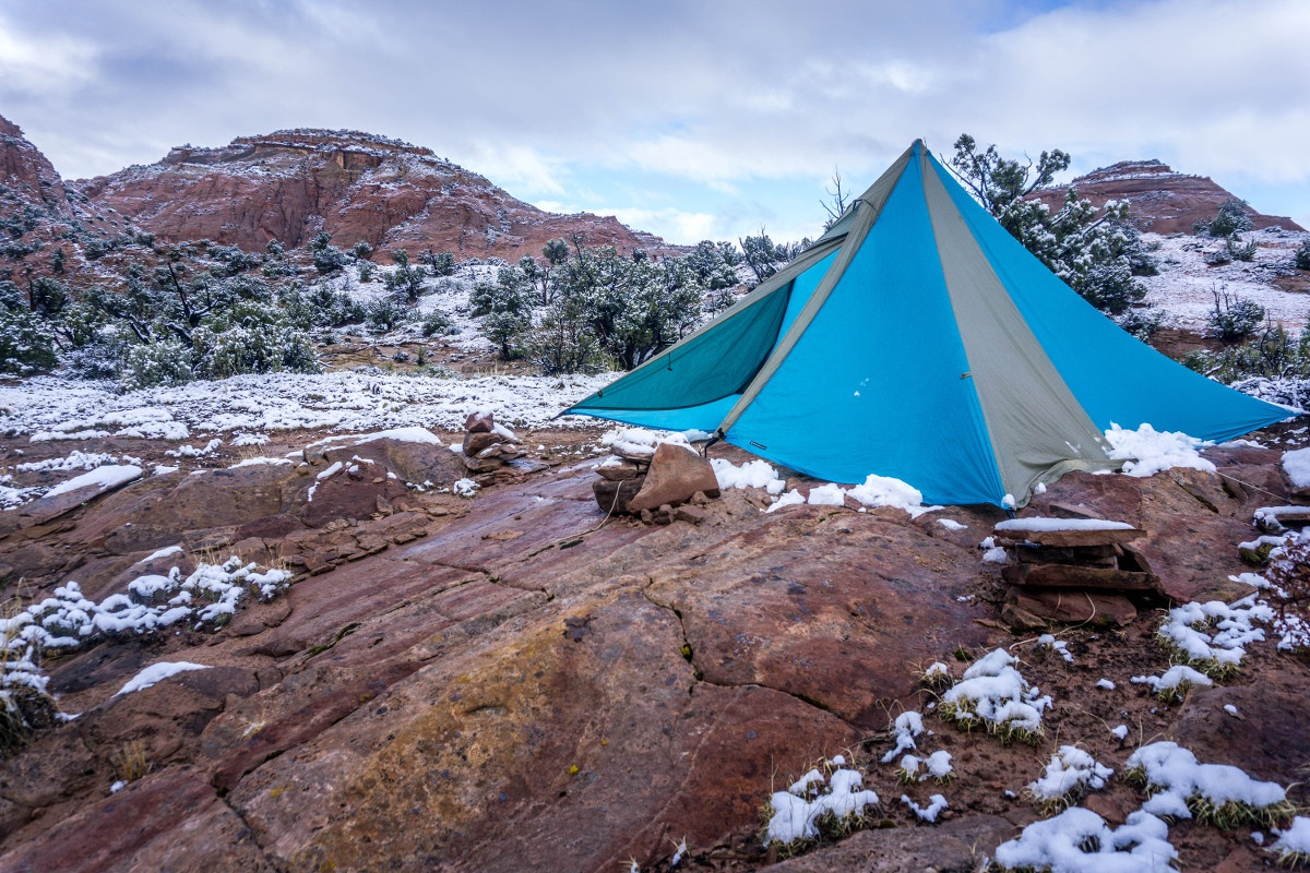 Blue and tan mega mid tent pitched on red rock with patchy snow