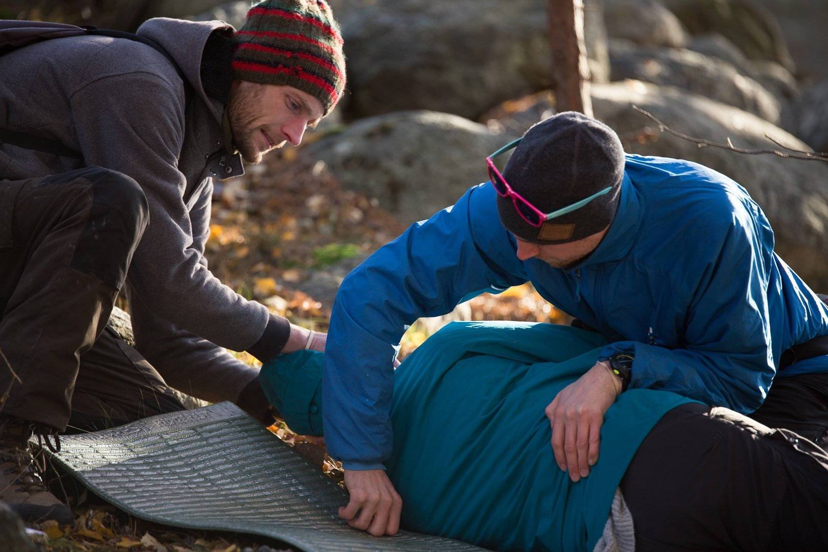 two NOLS Wilderness Medicine students care for a patient lying on his side on a camp pad