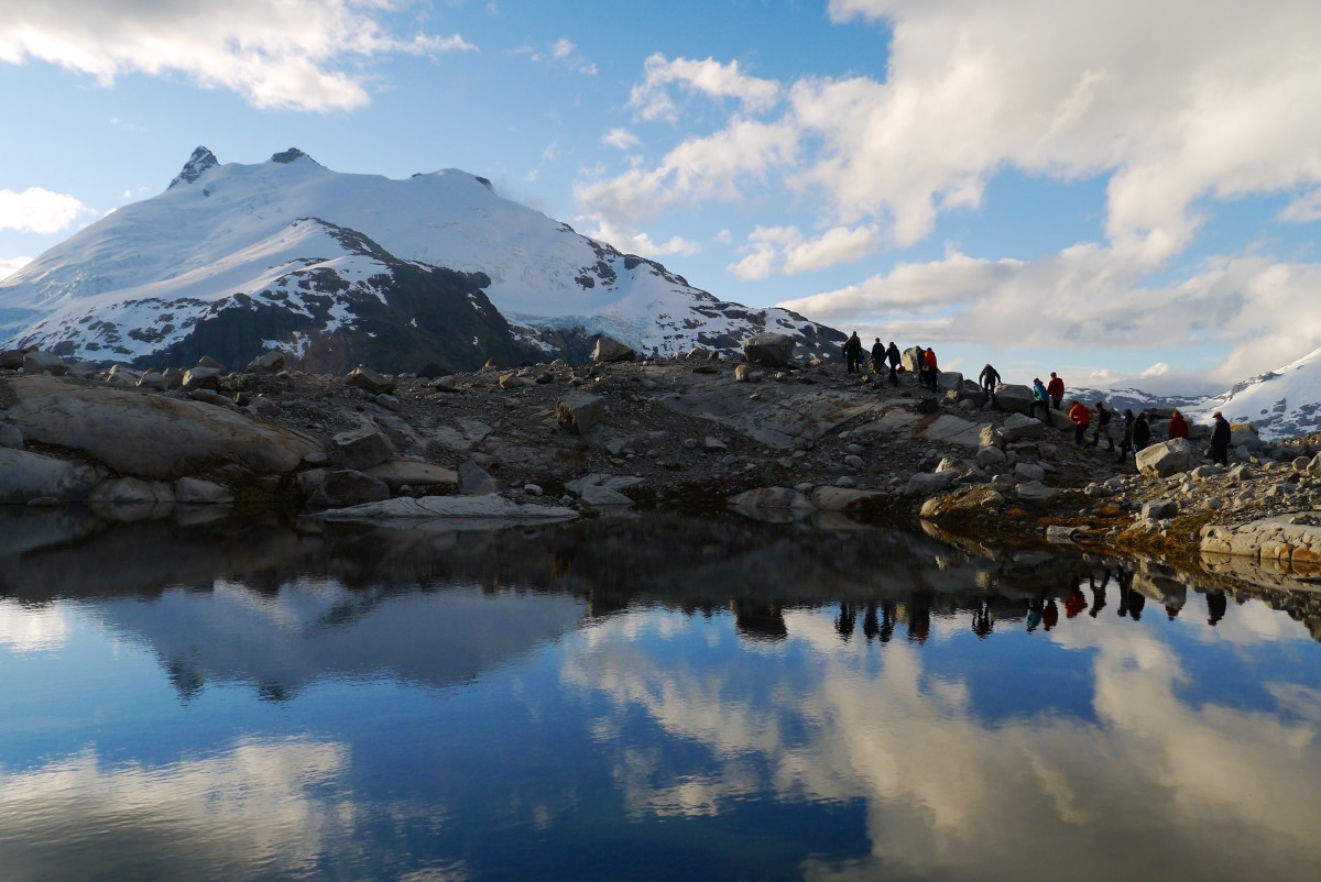 distant figures hike up a rocky slope toward snowy mountains surrounding a glassy lake with clouds reflected on its surface