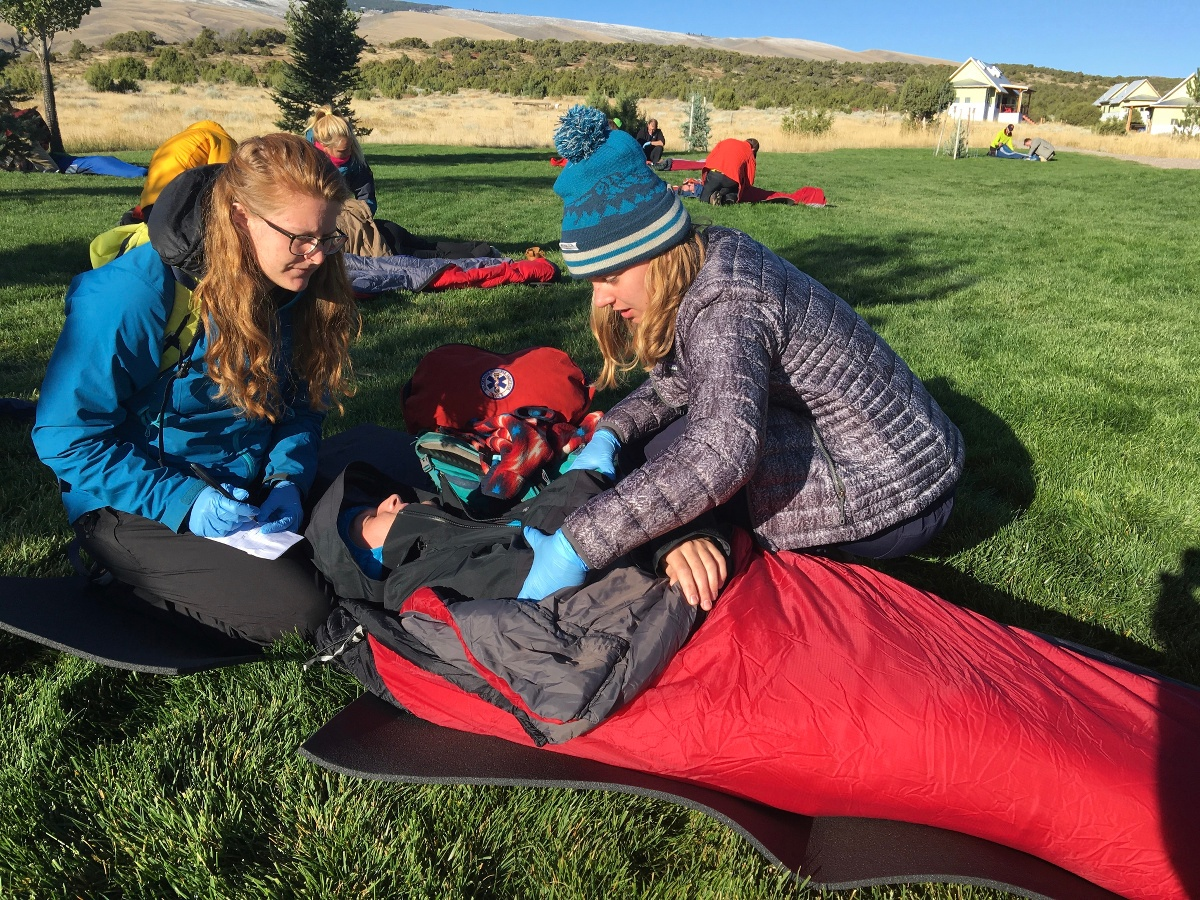 two female wilderness medicine students practice caring for a patient lying in a sleeping sleeping bag outdoors