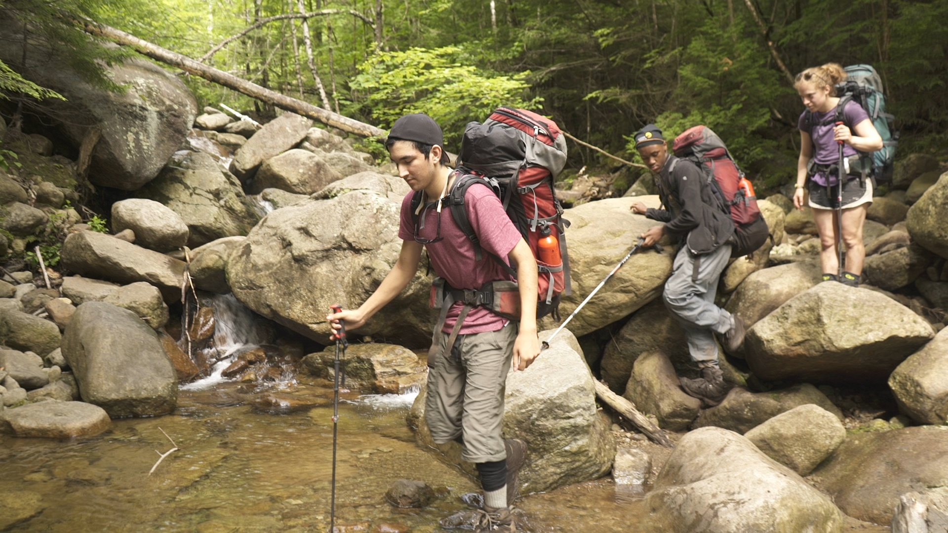 students wearing backpacks use trekking poles to cross a rocky creek in the Adirondacks