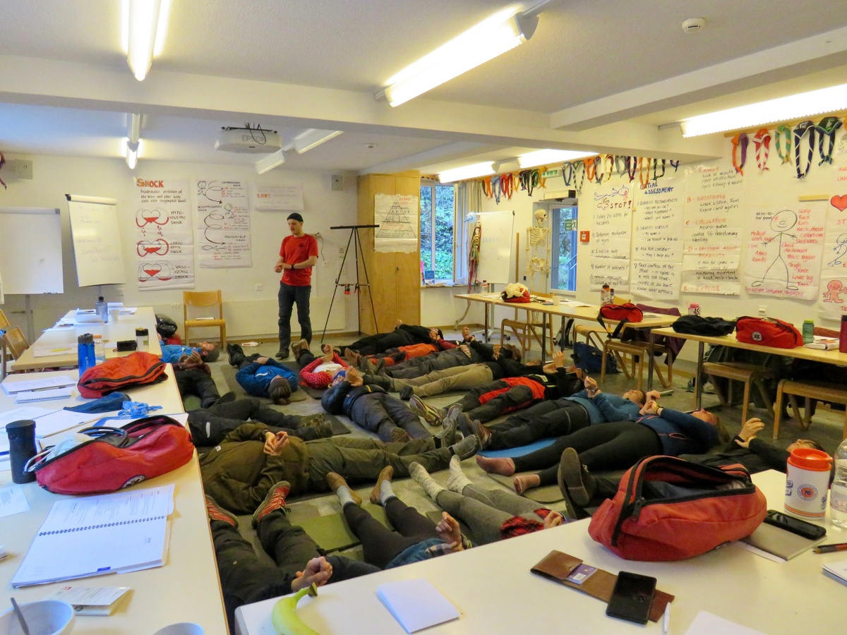 NOLS Wilderness Medicine students line on their backs on the floor of a classroom surrounded by desks