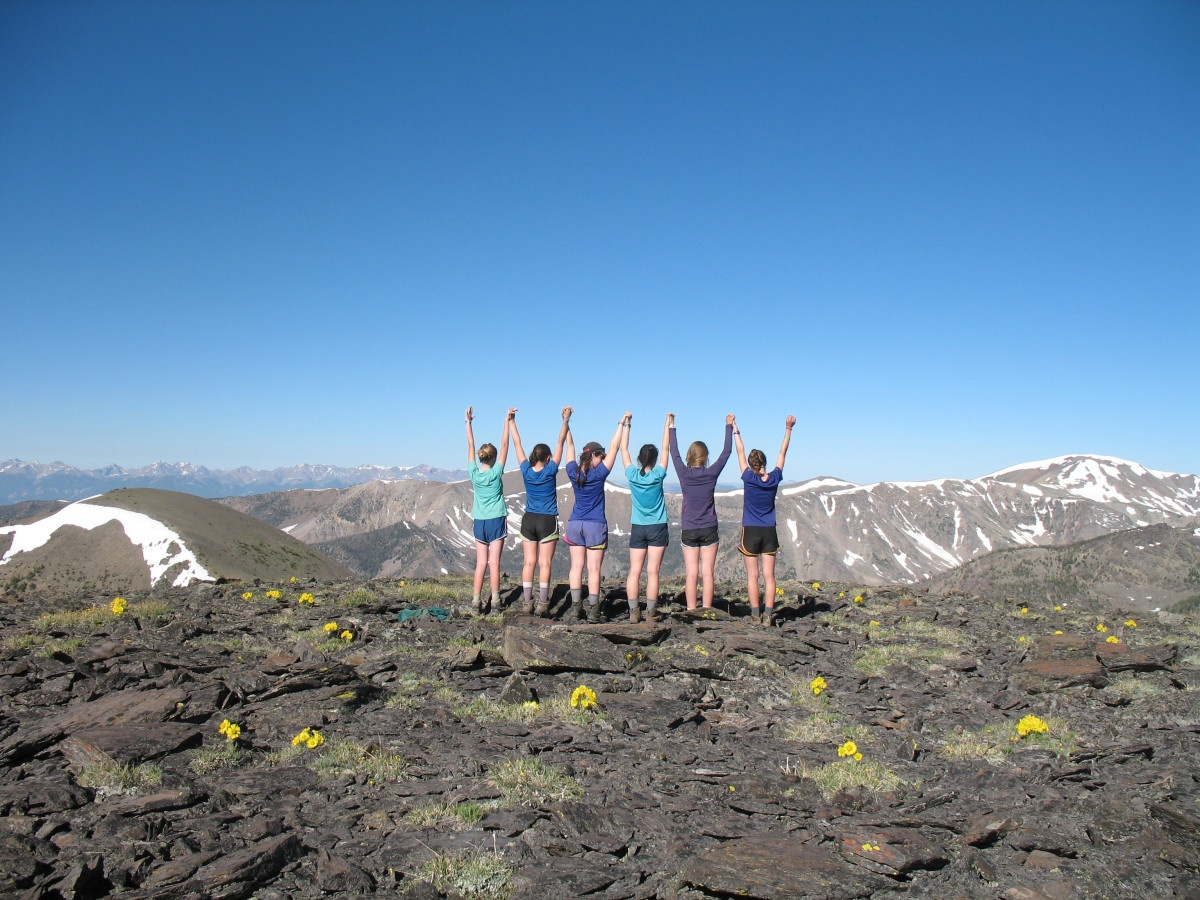 Six teenage girls stand together on a rocky expanse in the mountains and raise their arms up holding hands