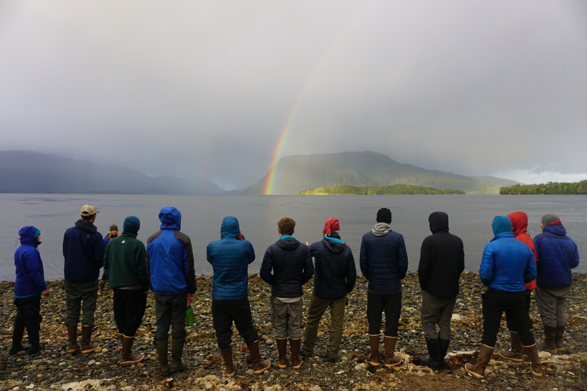 group of NOLS participants stand on a rocky beach looking out at a rainbow coming out of the mist