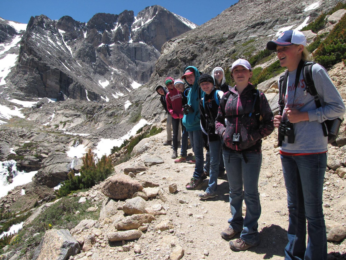 smiling teens stand in a line along a rocky trail in mountains dotted with snow patches
