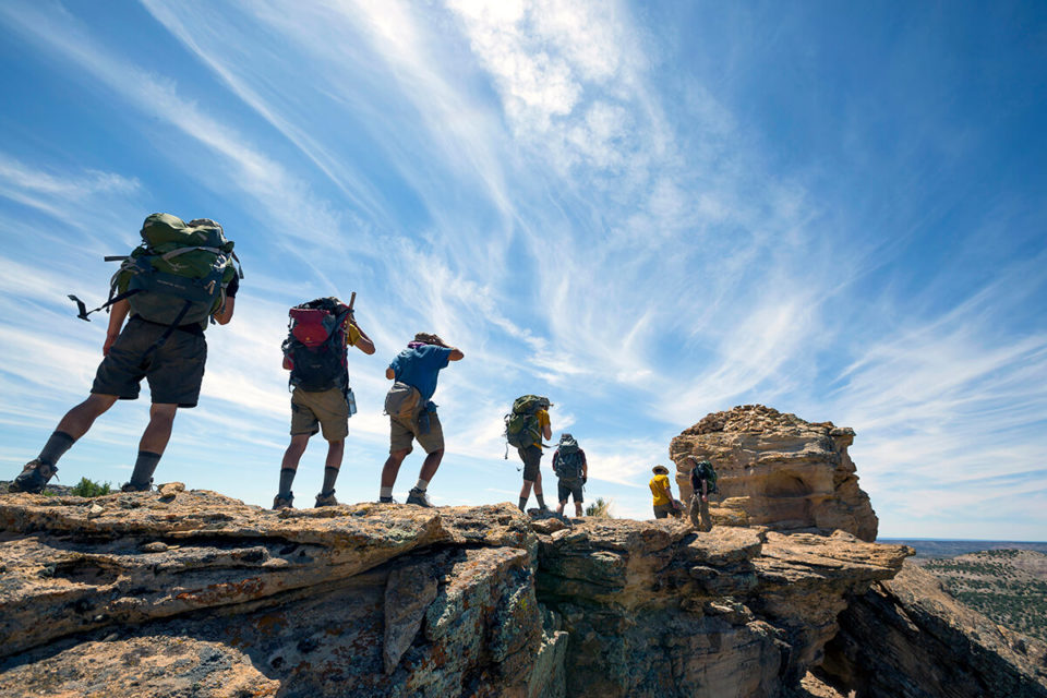 line of hikers wearing backpacks walk single file along a rocky outcrop