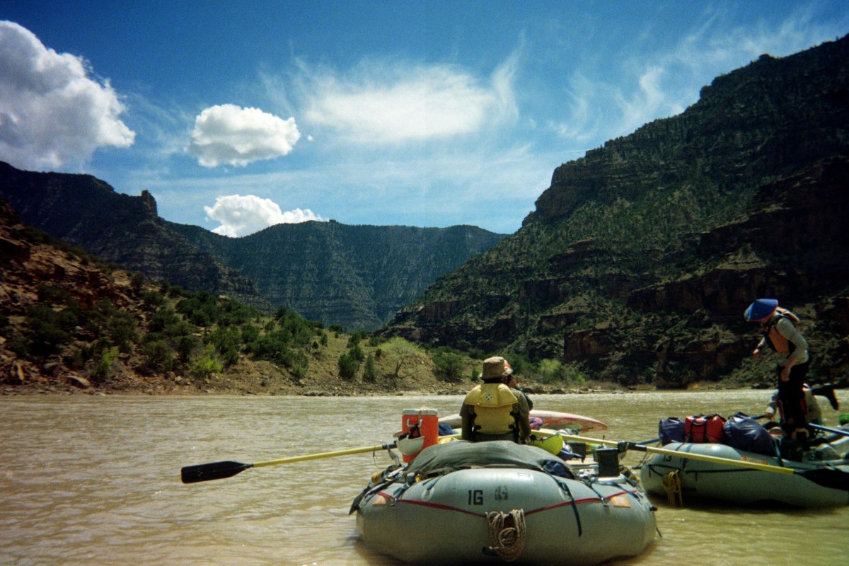 Students in two rafts with oars on a muddy river with tall canyon walls