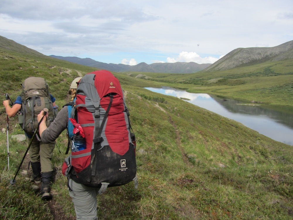 two students wearing backpacks use trekking poles to hike across a grassy slope in Alaska with glassy river to the right