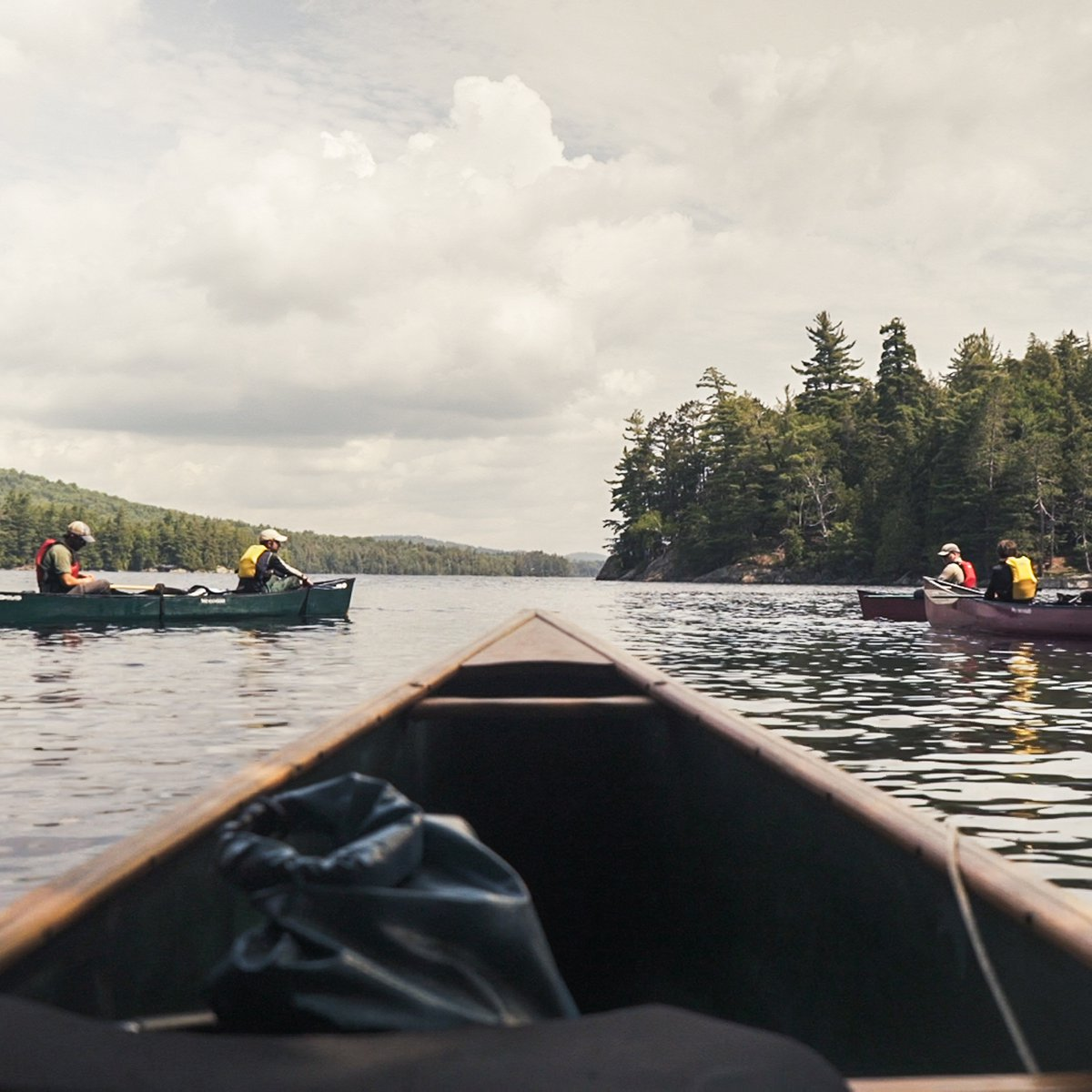 several canoes on calm lake in the Adirondacks as seen from the bow of a canoe