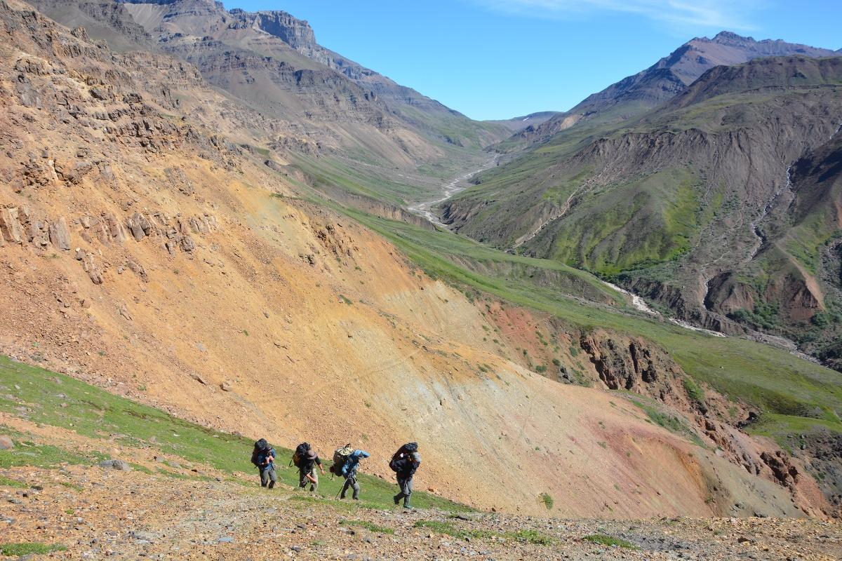 four students hike across steep terrain in Alaska's mountains