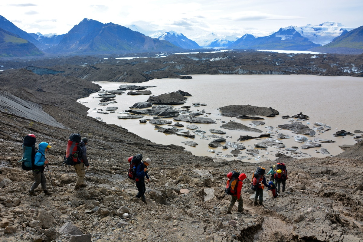 Hikers descending a talus field toward a muddy lake in Alaska's mountains