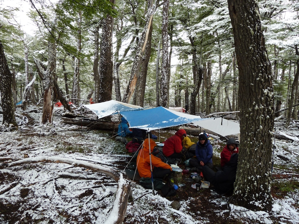 Students huddle under tarps to cook in a forest dusted with snow
