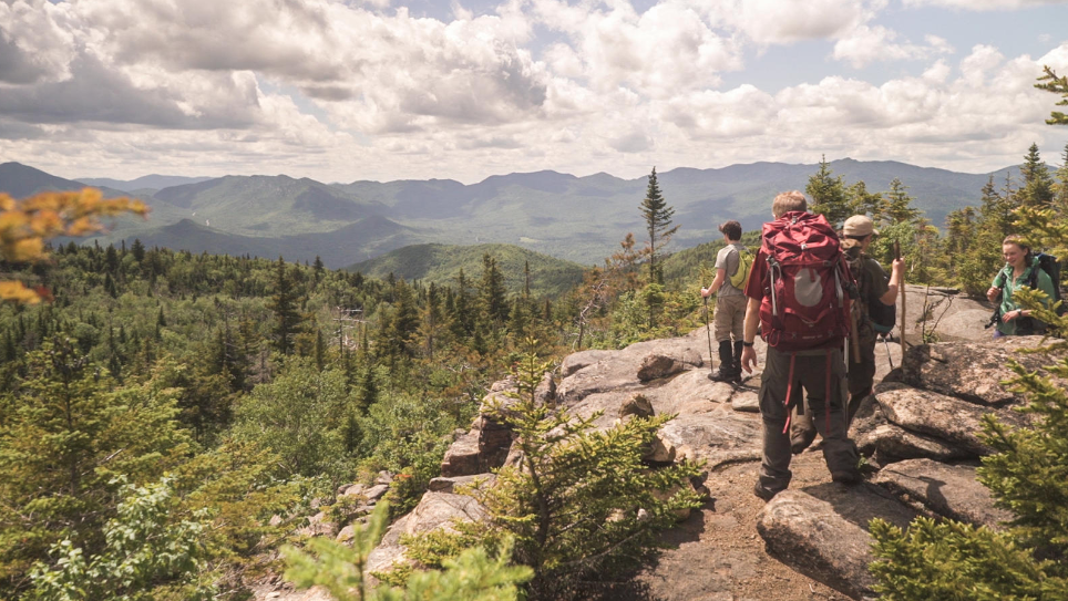 A group of four teenagers backpacking stop on a ridge overlooking rolling green mountains