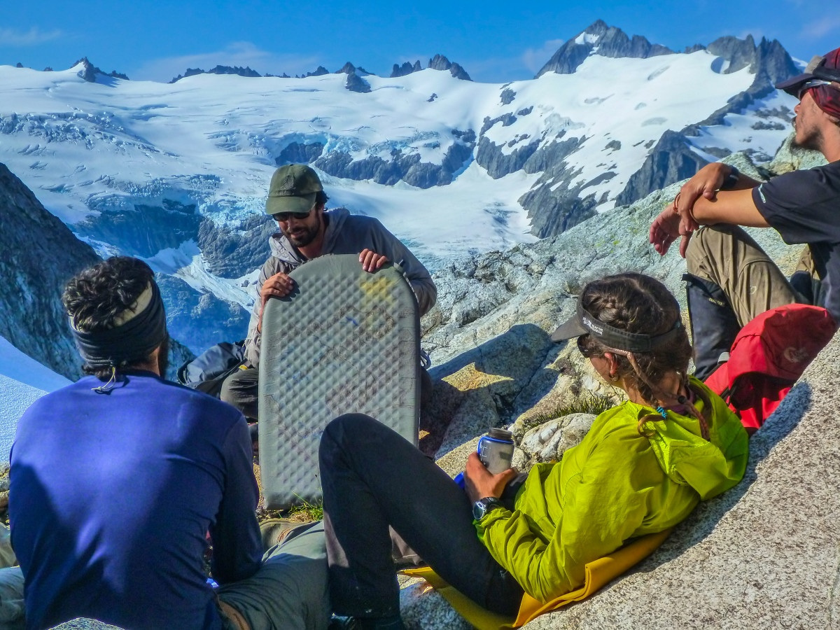 NOLS instructor holding foam pad teaches a lesson to students seated on a rocky outcrop in snowy mountains