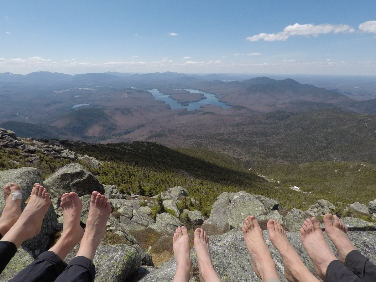 Five sets of soggy feet getting some sunshine at the top of a rocky slope looking down on a lake and forest