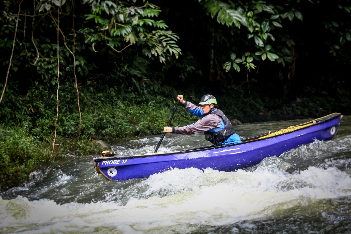 Woman paddles a purplish blue canoe through whitewater in Costa Rica
