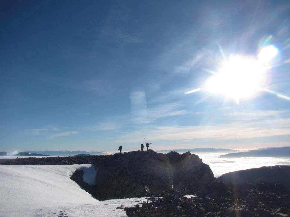 Three distant silhouetted figures on a ridge surrounded by snow on a sunny day